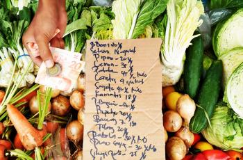 A local market vendor displays a list that shows the prevailing retail price of freshly harvested vegetables. (Photo from BusinessMirror)